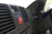 View along a car dashboard with focus to the red hazard warning button