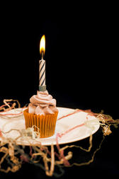 Burning candle on an orange cupcake with decorative icing to celebrate Halloween or a childs birthday