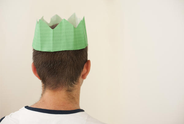 a man wearing a paper party hat from a christmas cracker