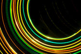 a pattern of green orange and yellow light trails moving around a central out of frame point