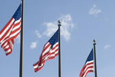 Three flagpoles flying the Stars and Stripes, the official national flag of the United States Of America.