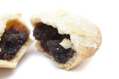 Partially eaten mince pie showing the spicy rich fruity filling and freshly baked golden crust, close up view
