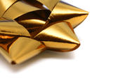 Close up of an ornate metallic gold bow used as a decoration during gift-wrapping and packaging of Christmas gifts or presents for a special occasion
