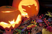 two carved halloween pumpkin lantern and a wreath of seasonal autumn berries and leaves