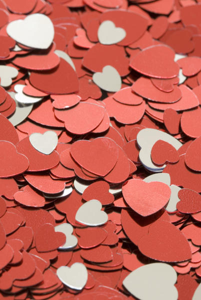 a background image featuring reflective heart shaped confetti in metallic silver and red colours