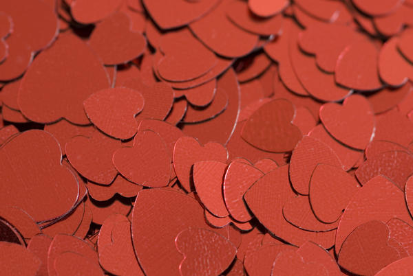 a background of metallic red heart symbols