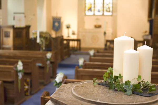a view of the inside of a church, decorated with white flowers and white church candles