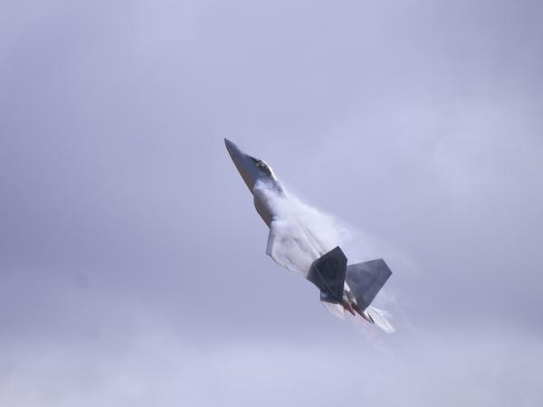 During an air show at high speed the Lockheed Martin F-22 Raptor creates vapor trails from leading flight surfaces