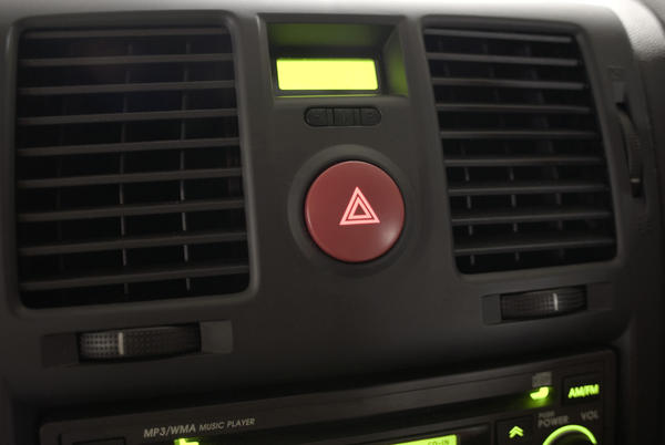Background of a car dashboard with focus to the central red hazard warning light