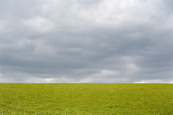 Empty green grassy field under an ominous cloudy grey sky