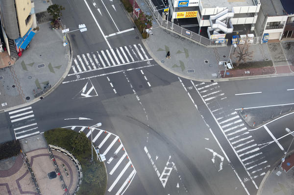 Aerial view of an empty street intersection in central Osaka, Japan showing traffic markings and crossings