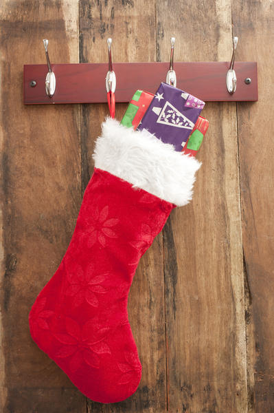 Colorful red Christmas stocking filled with small gifts hanging from a metal hanger on a wooden wall with copyspace