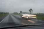 a car speeding down the road in the oppposite direction
