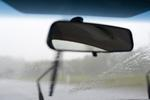 rear view mirror of a car driving on a rainy day